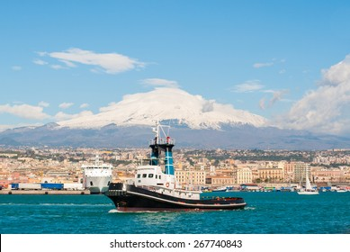 A tug boat leaving the harbor of Catania. Volcano Etna in the background