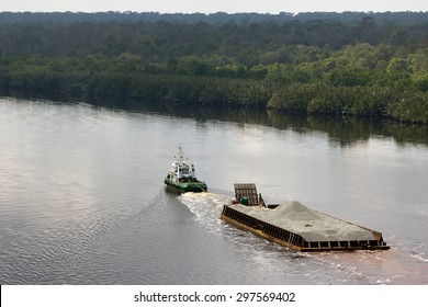 A tug boat pulling a pontoon on the river Sunga Belait, Brunei
