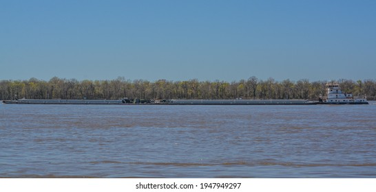 A Tug Boat is pushing Barges down the Mississippi River past Millington in Shelby, Tennessee