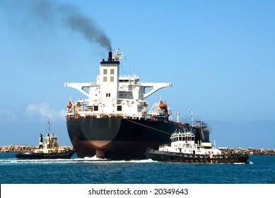 Tug boats guiding a cargo ship out of a harbour entrance