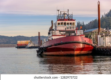 Tug boats moored in Rainier Oregon harbor countryside.
