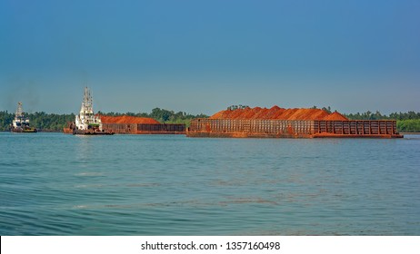 A tug boats pulls a large cargo barges transporting bauxite ore for offshote transshipment in Kamsar, Guinea.