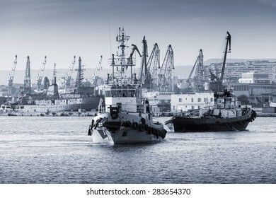 Tug boats are working in Varna harbor. Black Sea, Bulgaria. Vintage stylized photo with monochrome blue tonal photo filter