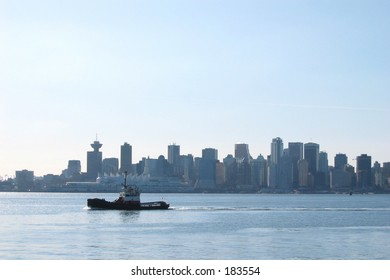 Tug crossing the water infront of downtown Vancouver.