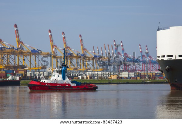 tug with heavy ship in the harbor