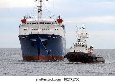 Tug helping general cargo ship to enter in port