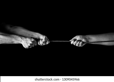 Tug war, man and woman pulling rope in opposite directions unequally, uneven. copy space