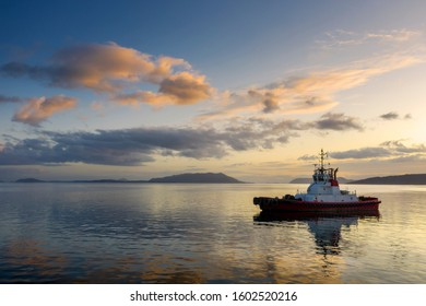 Tugboat Anchored in the San Juan Islands During a Beautiful Sunset. Tugboats escort oil tankers through the San Juan Islands to prevent accidental spills and groundings.