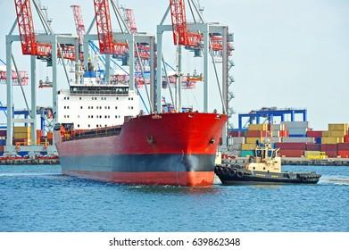 Tugboat assisting bulk cargo ship to harbor quayside