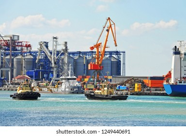 Tugboat assisting container cargo ship in harbor quayside