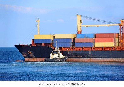 Tugboat assisting container cargo ship to harbor quayside