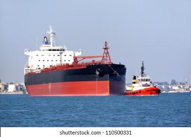 tugboat assisting huge vessel