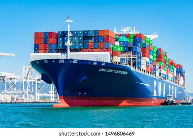 Tugboat assists French container ship CMA CGM JEFFERSON out of the port under blue sky. A tugboat maneuvers vessel by pushing, pulling or towing containership - Oakland, CA, USA - Circa, 2019