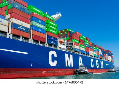 Tugboat assists French container ship CMA CGM out of the port under blue sky. A tugboat maneuvers vessel by pushing, pulling or towing containership - Oakland, California, USA - Circa August, 2019