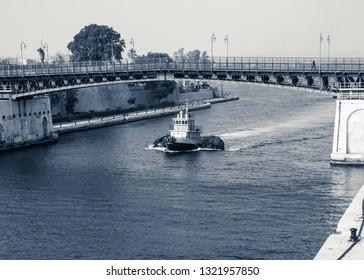 Tugboat with big rubber dinghies crosses the revolving bridge in Taranto, Italy, interpretation of the monochromatic shot.
