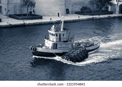 Tugboat with big rubber dinghies transits to the sea, interpretation of the monochromatic shot.