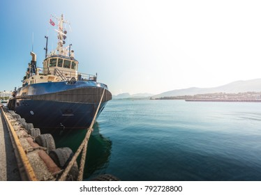 Tugboat or fishing boat in docks of Alesund, Norway, Europe. Ship in foreground and blue sky and mountains in background. Scandinavia travel.