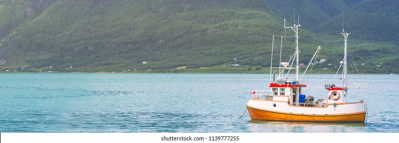 Tugboat or fishing boat at fiord in Norway, Europe. Ship in foreground and mountains in background. Scandinavia travel.