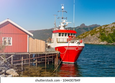 Tugboat or fishing boat at pier, Norway, Europe. Ship in foreground and blue sky and mountains in background. Scandinavia travel.
