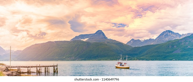 Tugboat or fishing boat at sunset in Norway, Europe. Ship in foreground and blue sky and mountains in background. Scandinavia travel.