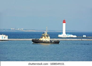 Tugboat in harbor quayside, near lighthouse in Odessa, Ukraine