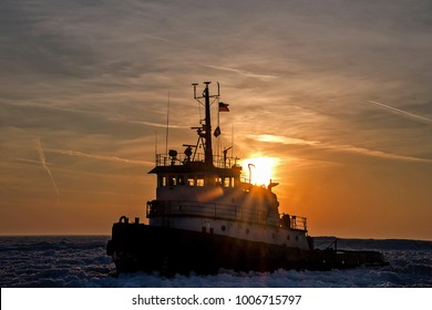 tugboat in Lake Michigan ice at sunset