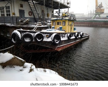 Tugboat moored. Heavy snow in harbor. Stormy weather