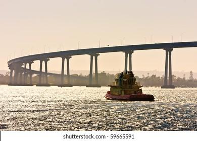 Tugboat near the San Diego - Coronado Bridge, locally referred to as the Coronado Bridge crossing over San Diego Bay in the United States, linking San Diego, with Coronado, California.