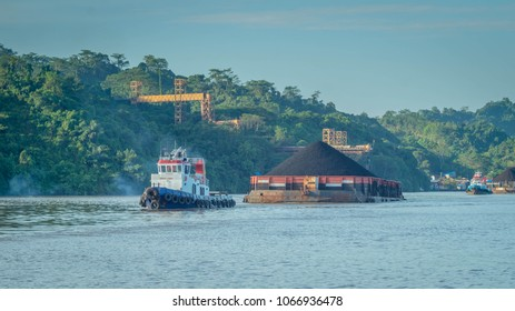 Tugboat pulling heavy loaded barge of black coal in the Mahakam river, Indonesia