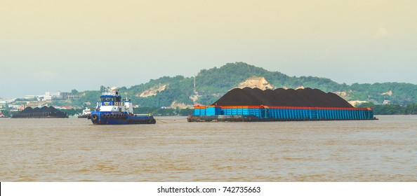 tugboat pulling heavy loaded barge of coal cruising Mahakam River in Samarinda, Indonesia