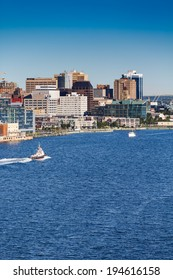 A tugboat sailing past the city of Halifax, Nova Scotia in blue water