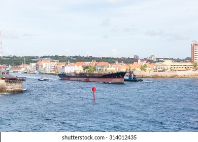 Tugboats pulling huge tanker from the harbor in Curacao