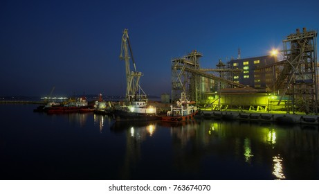tugs and a crane in the night port