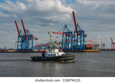 Tugs in front of the harbor cranes in Hamburg on the Elbe
