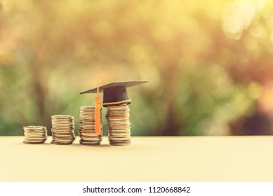 Tuition payment or tuition fee or expense for graduate study abroad program concept : Black graduation cap on stacks of coins, depicts fees charged by education institution for instruction or services