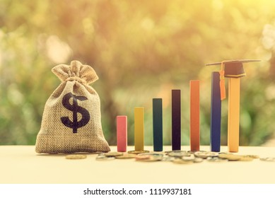 Tuition payment or tuition fee for graduate study abroad program concept : Black graduation cap on bar graph and a dollar bag, depicts fees charged by education institution for instruction or services