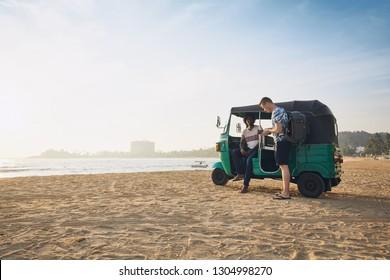 Tuk tuk driver with passenger against sand beach and sea in Sri Lanka.
