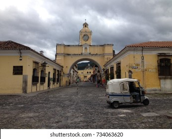Tuk Tuk driving past the Santa Catalina arch in Antigua, Guatemala.