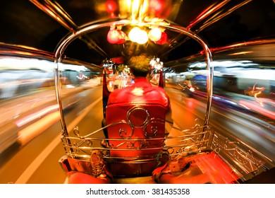 Tuk tuk on the road at night in Bangkok.
