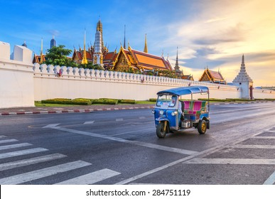 Tuk Tuk is parking in front of Wat Phra Kaeo or Grand Palace, Bangkok, Thailand. This is a beautiful scene of the palace with the twilight sky.