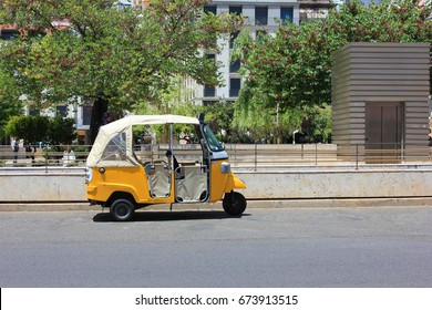 Tuk tuk small passenger three weel mini car isolated on summer empty street road background. Bright yellow rickshaw driven by locals helps tourists to travel around the city fast and cheaper than taxi