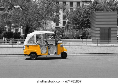 Tuk tuk small passenger three wheel mini car isolated on summer empty city center street road view. Black and white photography pattern selective color picture texture with empty copy space background