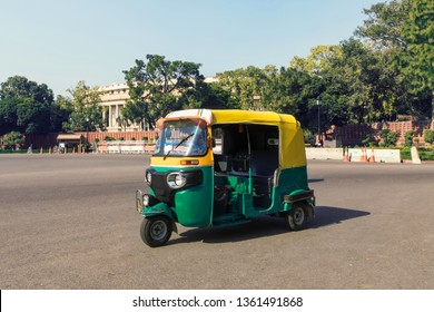 Tuk tuk - traditional indian moto rickshaw taxi on one of the street of New Delhi. yellow green tricycle stands on the square against the background of the presidential Palace. motorcycle 50-60 years