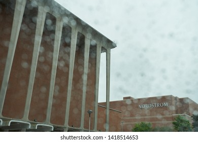 Tukwila, Washington, USA - May 25, 2019: The NORDSTROM sign seen through car window at the Nordstrom Southcenter parking lot on a rainy day.