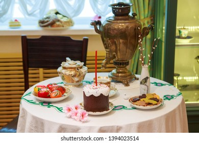 Tula city, Russia - May 2019: beautiful samovar, cookies, willow, easter cake with festive candle and colored eggs are on the table with white tablecloth in the museum of samovars.