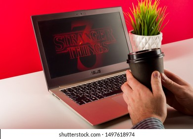 TULA, RUSSIA -AUGUST 18 2019: Stranger Things 3 from Netflix TV series Poster, the laptop on dask with shot of Stranger Things Season 3. Men's hands are holding a paper cup with coffee
