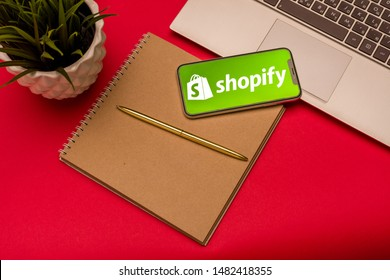 Tula, Russia - AUGUST 19, 2019: Shopify logo on iphone X on keyboard laptop on red background