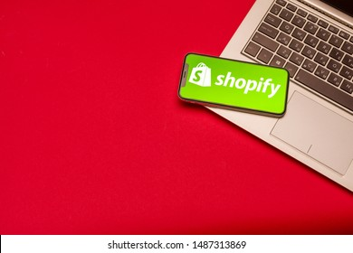 Tula, Russia - AUGUST 19, 2019: Shopify logo on iphone X on keyboard laptop on red bsckground