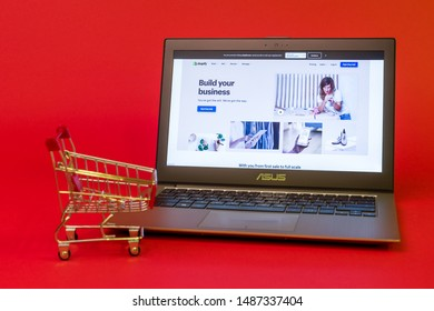 Tula, Russia - AUGUST 19, 2019: Shopify web page displayed on a modern laptop shopping cart on red background