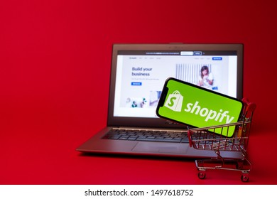 Tula, Russia - AUGUST 19, 2019: Shopify web page displayed on a modern laptop on red background. Shopify logo on iphone X in shopping cart